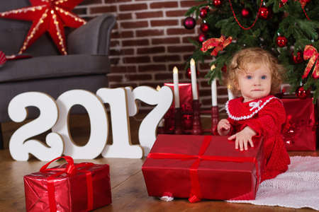 happy families: Cute smiling baby girl is wearing red fashion dress near beautiful xmas tree Stock Photo