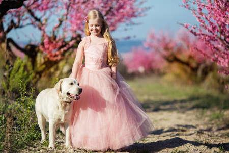 arbol de pascua: Niña con perro labrador en el jardín de flores Foto de archivo