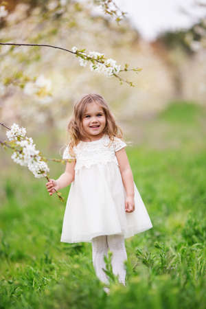 Pretty child girl in blossom spring garden Standard-Bild