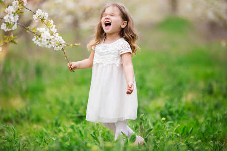 Nervous child girl in blossom garden