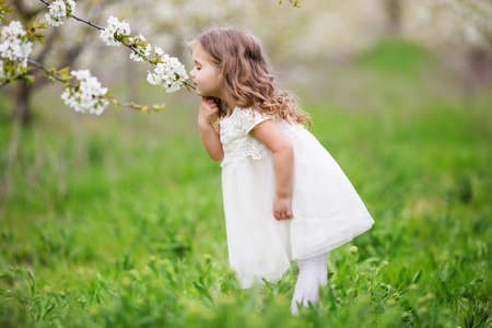 Pretty child girl is smelling flowers in garden