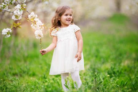 Pretty child girl in blossom spring garden Stockfoto
