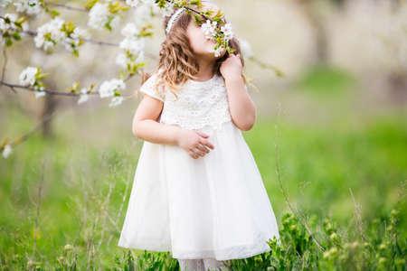 Pretty child girl is smelling flowers in garden