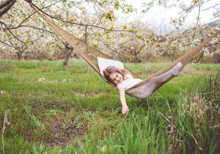 Child girl is resting in hammock outdoors Stockfoto