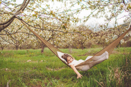 Child girl is resting in hammock outdoors Standard-Bild