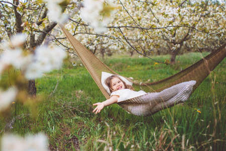 Happy child girl is resting in hammock outdoors