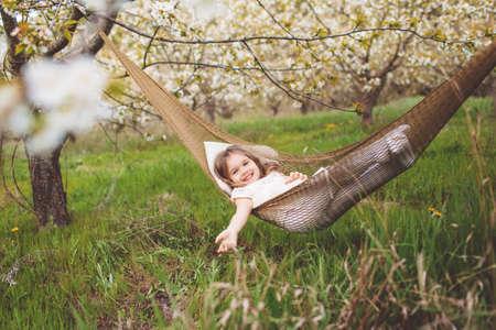 Happy child girl is resting in hammock in garden Stockfoto
