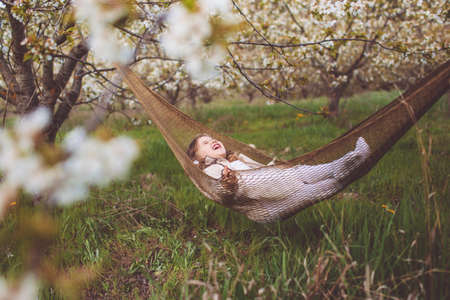 Happy child girl is resting in hammock in garden Standard-Bild