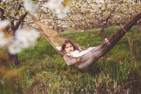 Child girl is resting in hammock in cherry garden Stockfoto