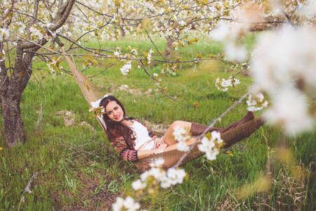 Woman is resting in hammock in cherry garden Stockfoto