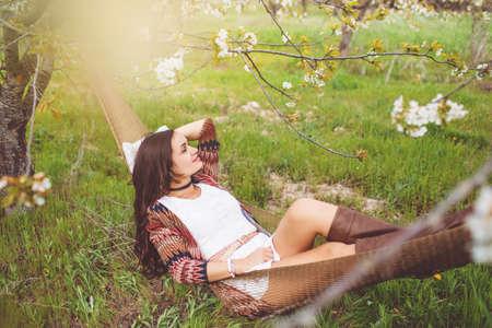 Woman is reading book in hammock in garden