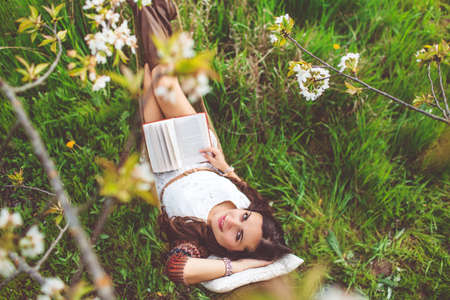 Woman is reading book in hammock outdoors