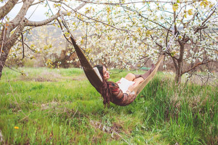 Woman is relaxing in hammock on the nature