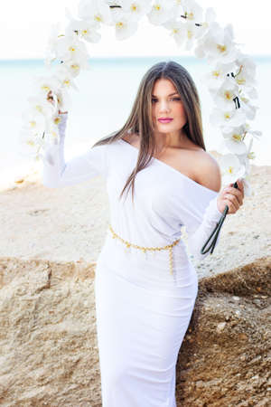 Portrait of beautiful brunette woman in white dress posing over sea view with white flowers photo