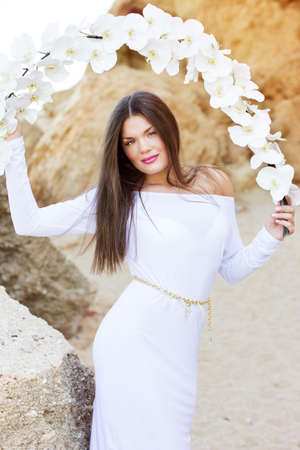 Portrait of beautiful brunette woman in white dress posing over sea coast with white flowers photo