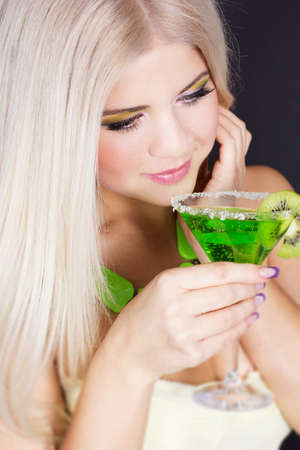 Sexy blonde gorl with green cocktail photo
