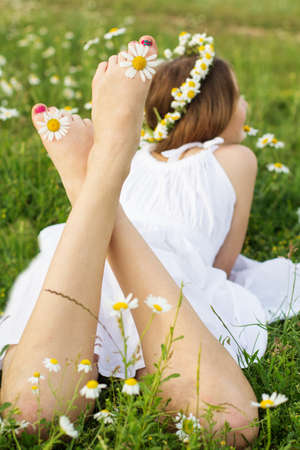 Feets picture of child girl is lying at  green camomile field photo