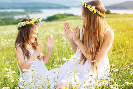 Cute child girls is playing at  green camomile field with mountains view photo