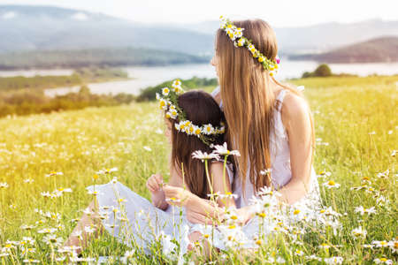 Cute child girls is sitting at  green camomile field with mountains view photo
