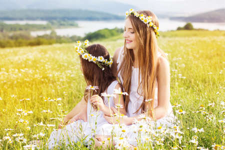 Cute sisters girls is playing at  green camomile field with mountains view photo
