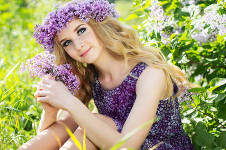 teen love: Beautiful blonde girl is wearing wreath of lilac flowers sitting on the nature, summer time Stock Photo