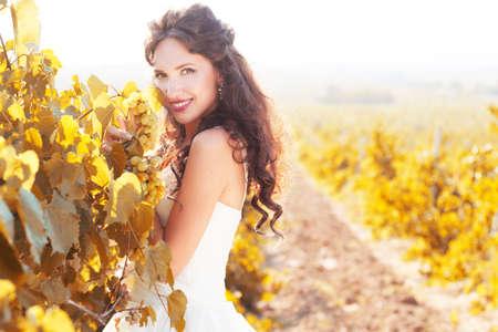 Bride wearing nice white dress is walking in an autumn vineyard