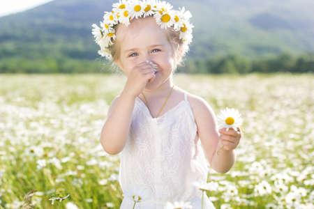 Cute little smiling girl in the chamomile field in spring Standard-Bild