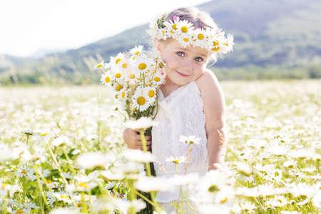 sonrisa: Ni�a sonriente linda en el campo de la manzanilla en la primavera de Foto de archivo