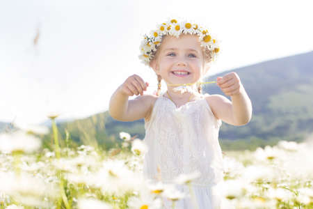 Cute little girl in the chamomile field in spring