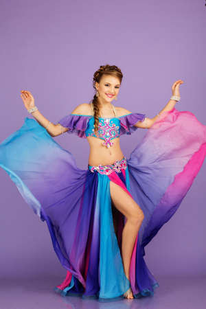 Beautiful belly dancer pretty girl is wearing a colorful fashion costume. Isolated on purple