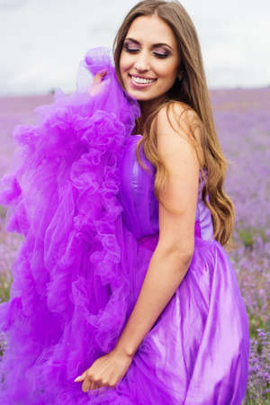 Beautiful smiling woman is wearing magic purple fashion dress posing at field of purple lavender flowers Standard-Bild