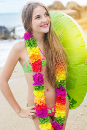 cute teen girl: Cute teen girl is wearing swimsuit and hawaiian colorful flowers walking at beach with green rubber ring Stock Photo