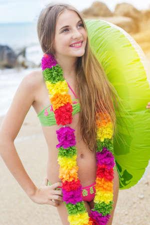 petite fille maillot de bain: Mignon adolescente porte maillot de bain et des fleurs colorées hawaïennes marcher sur la plage avec un anneau de caoutchouc vert