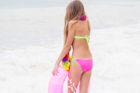 little girl barefoot: Cute child wearing swimsuit walking at beach with pink rubber ring