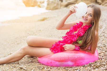 little girl barefoot: Cute smiling teen girl wearing swimsuit and pink flowers on her neck is sitting at beach on pink rubber ring Stock Photo