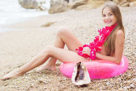sea shells on beach: Cute smiling teen girl wearing swimsuit and pink flowers is sitting at beach on pink rubber ring