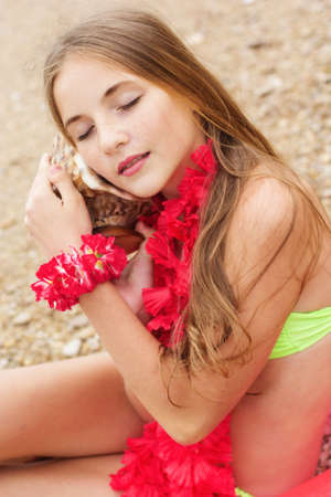 little girl barefoot: Cute teen girl wearing swimsuit and pink flowers is sitting at beach on pink rubber ring with shell in hands