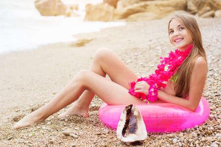 Симпатичные девушки подростка носить купальник и розовые цветы сидит на пляже на розовом резиновым кольцом