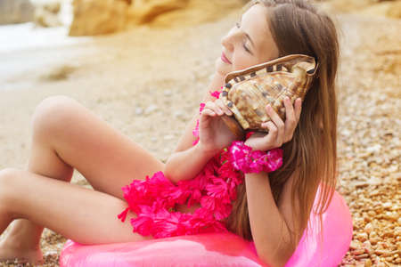 little girl barefoot: Cute teen girl wearing swimsuit and pink flowers is sitting at beach on pink rubber ring with seashell in hands