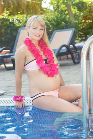 pink bikini: Beautiful pregnant woman is wearing pink hawaiian flowers sitting near swimming pool with blue water