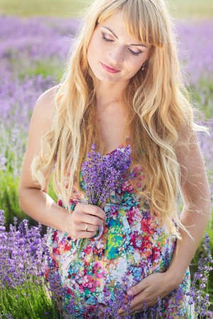 pregnant blonde: Beautiful pregnant blonde woman is wearing fashion colorful dress resting in the lavender field