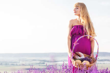 pregnant blonde: Beautiful pregnant blonde woman is wearing purple dress is holding basket with sweet buns