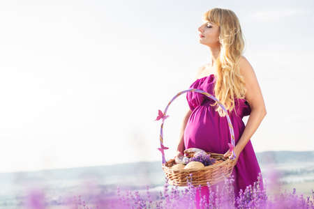 pregnant blonde: Beautiful pregnant blonde woman is wearing purple dress is holding basket with sweet buns and rolls