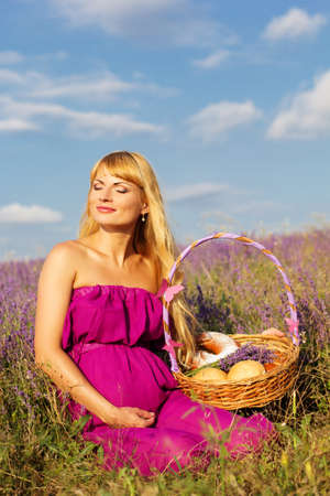 pregnant blonde: Beautiful pregnant blonde woman is wearing purple dress is holding basket with purple ribbon and sweet buns and rolls Stock Photo