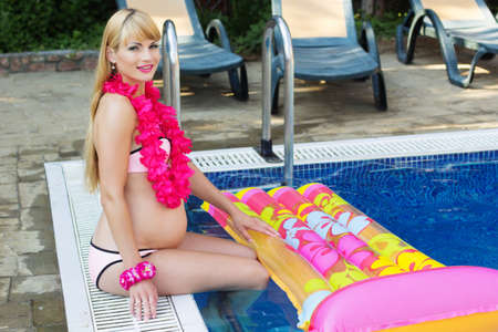 pregnant blonde: Beautiful pregnant blonde girl is sitting with colorful mattress and hawaiian flowers near blue water of swimming pool