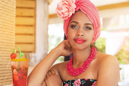 zulu: Young south african zulu woman is wearing fashion dress with makeup is sitting near bar and drinking mojito, summer time