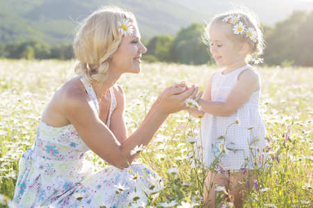 weisse kleider: Mutter mit niedlichen kleine Tochter tragen wei�e Kleider in der Kamillenfeld, Sommerzeit Lizenzfreie Bilder