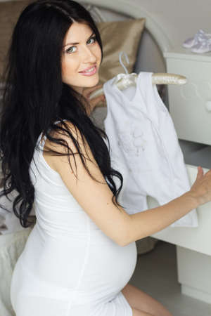 sexy belly: Beautiful pregnant woman is staying near chest of drawers and holding white babys clothes