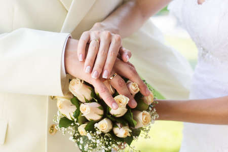 Bride and grooms hands with golden wedding rings on the bouquet with white roses