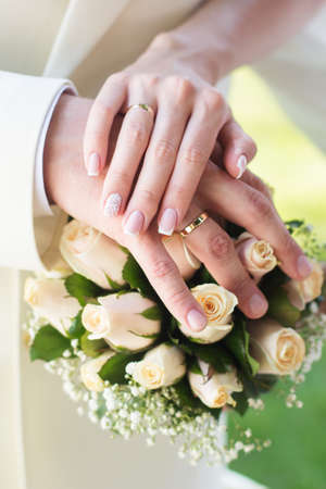 Bride and grooms hands with wedding rings on the bouquet with white roses